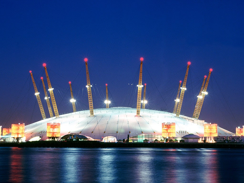 "Located right on the prime meridian and in the home of Greenwich Mean Time, London's Millennium Dome fittingly resembles a clock, with 12 yellow masts sticking up out of a gleaming white ""face"". (Project director Mike Davies was into astronomy, so the number 12 also references the months of the year and constellations in the zodiac.) Architects at the Richard Rogers Partnership took a beating in the press when it opened as part of the nationwide Millennium Festival, partially because of political posturing surrounding the project, but residents today still visit the Millennium Dome—rebranded the O2 Arena—to see concerts. It also hosted basketball and gymnastic events during the 2012 Olympic & Paralympic Games."